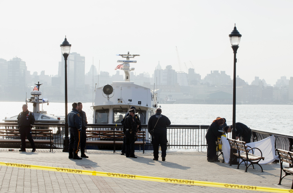Police investigate the scene Sunday after divers found the bodies of two men in the Hudson River near Sinatra Park in Hoboken, N.J. Police have not identified the victims.