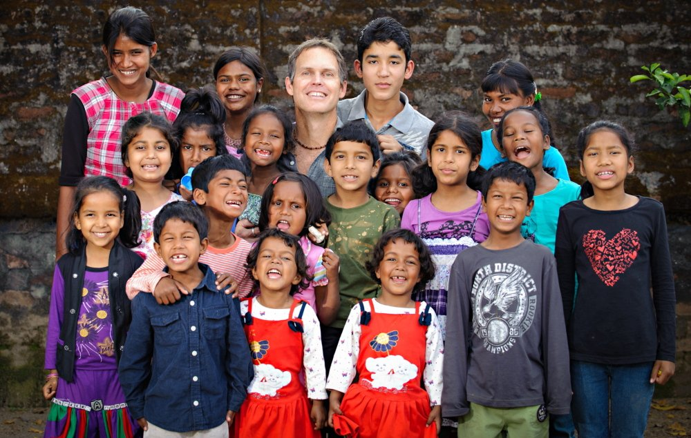 John Marshall poses with some of the kids at the mission who helped on his videos.