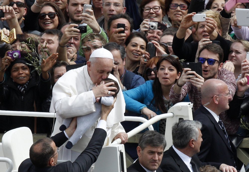 Pope Francis kisses a baby at the close of the Palm Sunday Mass in St. Peter's Square at the Vatican on Sunday.