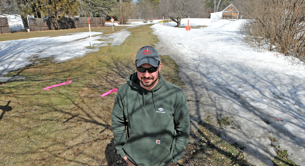 Todd Dixon, president of Solon Snow Hawks, stands by a snowmobile trail that crosses U.S. Route 201 in Solon on Saturday.