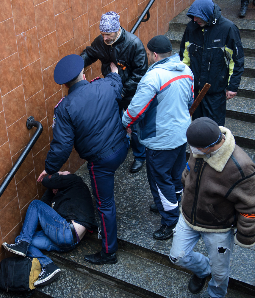 A police officer stops a pro-Russian activist who is charging toward a Ukrainian protester lying on the steps in Kharkiv on Sunday. But police have often proven unable or unwilling to repel pro-Russian gunmen and Moscow loyalists.