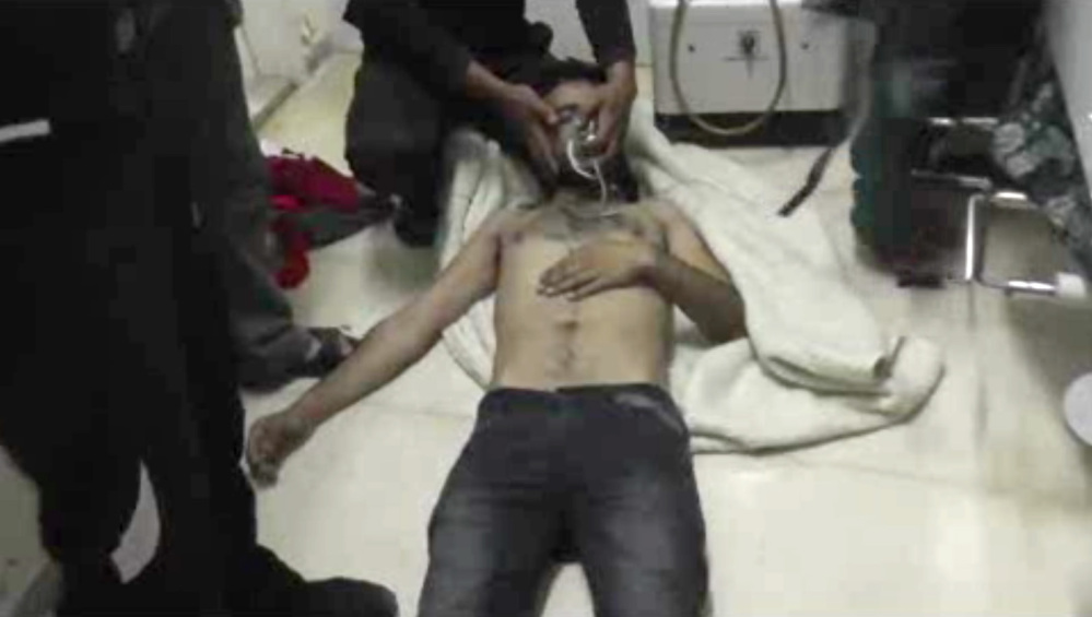 A man lies on the floor with an oxygen mask at a hospital room in Kfar Zeita, some 125 miles north of Damascus, Syria, on Friday.