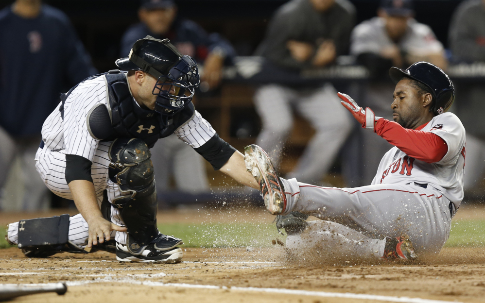 Yankees catcher Brian McCann tags out Boston's Jackie Bradley Jr. at the plate after a second-inning single by Grady Sizemore during New York's 3-2 win Sunday night.