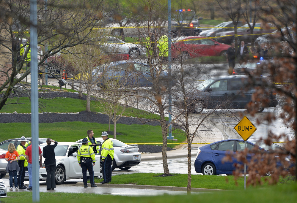 Kansas State troopers stand near the location of a shooting Sunday at the Jewish Community Center in Overland Park, Kan.