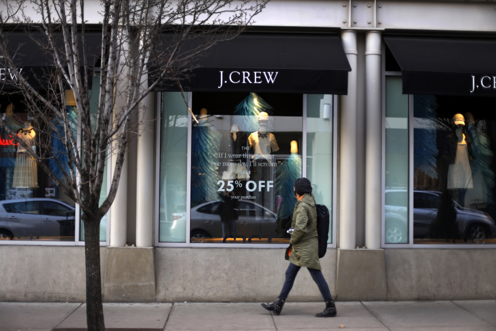 In this March 24, 2014 photo, a pedestrian passes a J.Crew store in the Shadyside shopping district of Pittsburgh. The Commerce Department reports on retail sales for March on Monday, April 14, 2014.