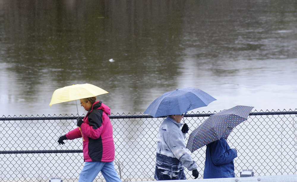 Walkers along the Kennebec River Rail Trail shelter themselves from rain Sunday from raindrops alongside the Kennebec River in Farmingdale. The National Weather Service issued a flood watch for Kennebec County through Wednesday as temperatures are expected to rise Monday with showers approaching Tuesday.