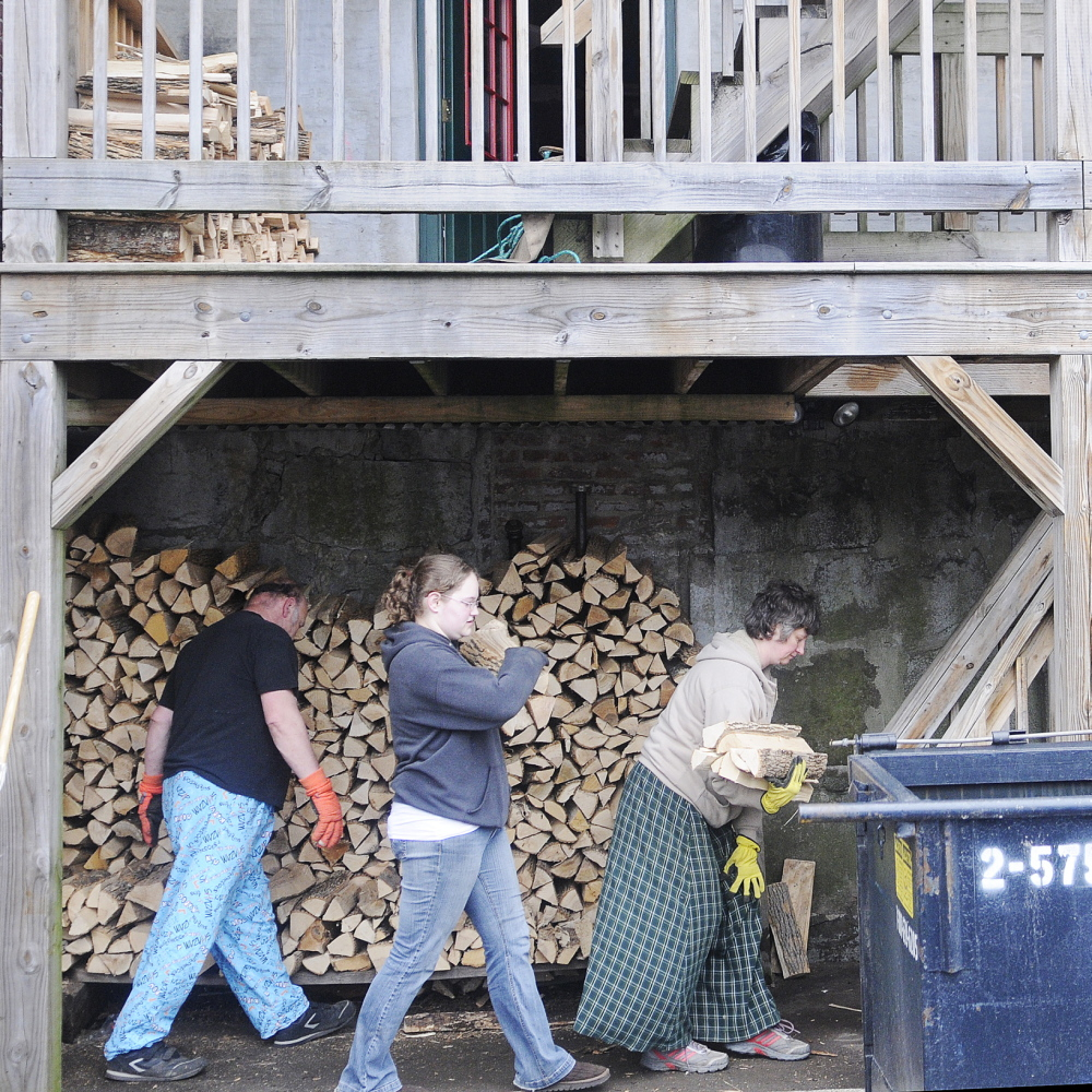 Donald Hallett, his daughter, Cassandra, and wife, Suzette, carry kiln-dried firewood Tuesday up to the first floor deck of Kennebec Pizza ahead of high water expected to come up over the banks of the Kennebec River. Kennebec Pizza stores the firewood for its ovens beneath the building on the shores of the river.