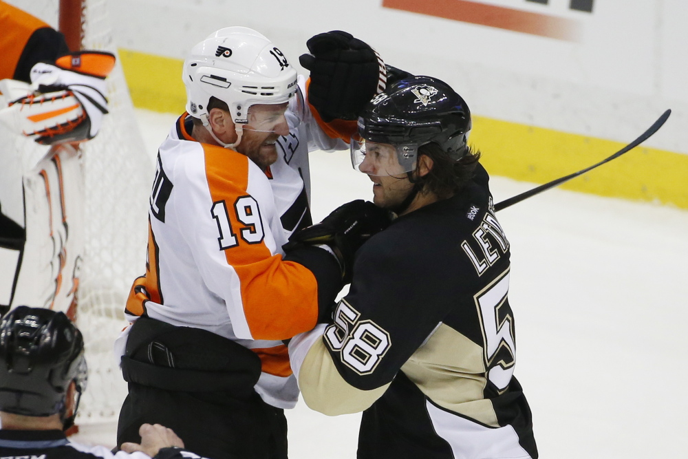 Pittsburgh Penguins' Kris Letang tangles with Philadelphia Flyers' Scott Hartnell in Saturday's hockey game in Pittsburgh. A class-action lawsuit filed by three retired players accuses the league of encouraging fights.
