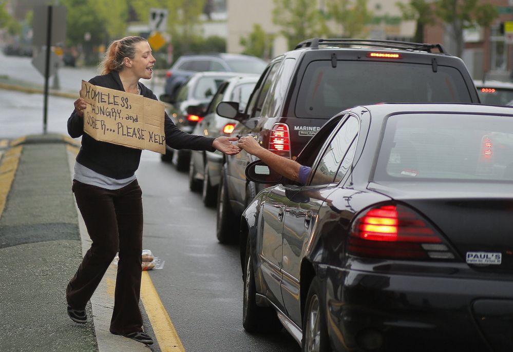 Alison Prior, 29, of Portland, receives change from a driver while she panhandles at the corner of Preble Street and Marginal Way last May. The city of Portland says panhandling interferes with public safety.