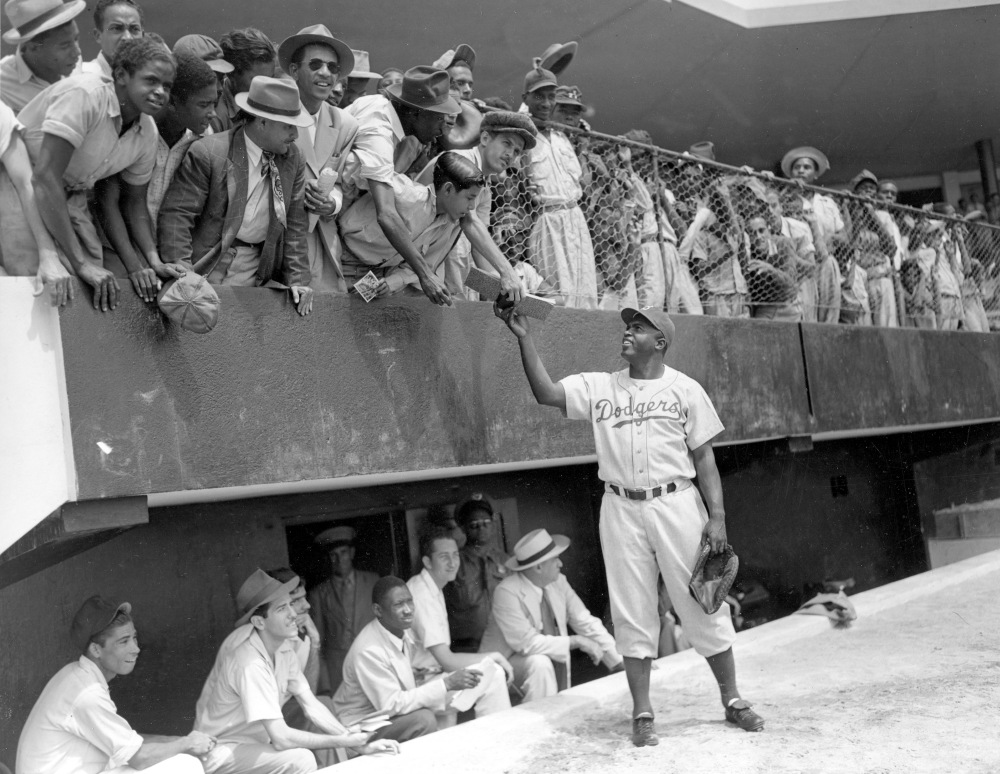 Jackie Robinson, first baseman of the Brooklyn Dodgers, returns an autograph book to a fan in the stands on March 6, 1948, during the Dodgers' spring training in Ciudad Trujillo, now Santo Domingo, in the Dominican Republic.