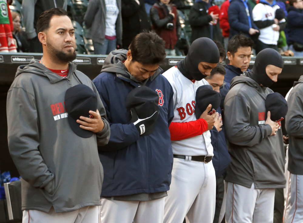 Members of the Boston Red Sox stand for a moment of silence for the victims of the Boston Marathon bombings, before the game against the Chicago White Sox on Tuesday in Chicago.