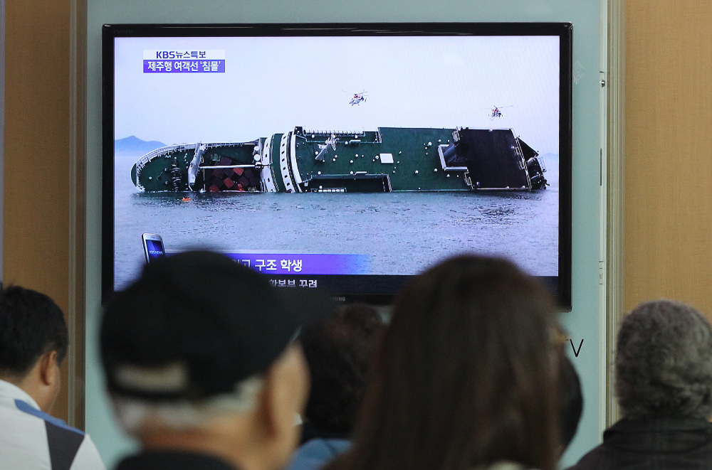 People at the Seoul Railway Station watch a TV news program showing the sinking ship Wednesday.