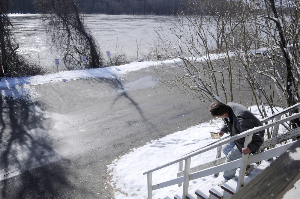 Patty Burnett measures the steps on the entrance of her Hallowell business, Dom's Barbershop, Wednesday morning to determine how high the Kennebec River will have to rise to enter her building on Water Street. Burnett estimated that the Kennebec will have to reach 22 feet to flow into the basement. The river is forecast to rise to 19 feet by Wednesday evening, according to the National Weather Service.