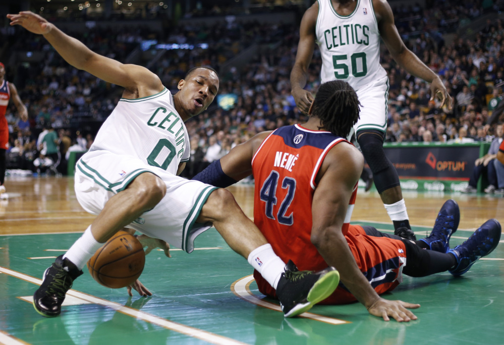 Boston Celtics guard Avery Bradley (0) loses his footing during a scramble for the ball with Washington Wizards forward Nene Hilario (42) during the first quarter of an NBA basketball game in Boston, Wednesday, April 16, 2014.