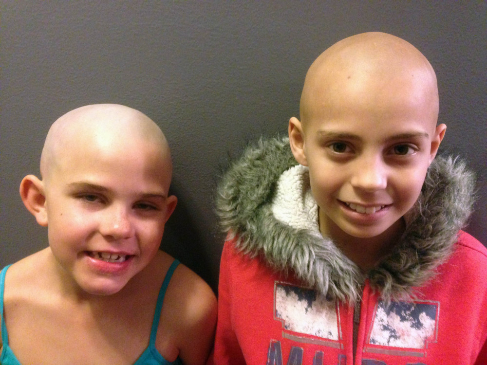 Kamryn Renfro, 9, left, and Delaney Clements, 11, right, stand together for a photo last month in Grand Junction, Colo., shortly after Kamryn had her head shaved to support Delaney, who lost her hair after treatment for cancer. Kamryn was suspended from her public charter school in Grand Junction because a shaved head goes against the school's dress code. But the school quickly reversed the decision.