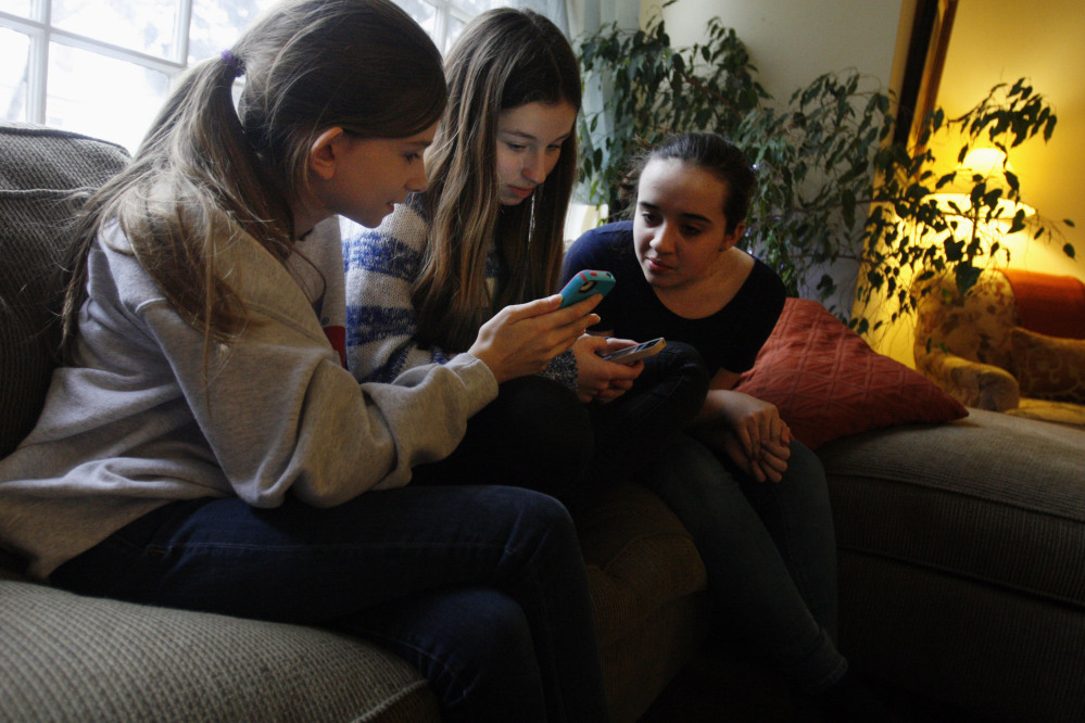 Kate McClintock, 12, left, Kate Green, 13, and Lilly Bond, 13, look at their smartphones at Lilly's home in Evanston, Ill., last week. The friends are seventh-graders at Haven Middle School in Evanston, which has been at the center of a controversy over its dress code.