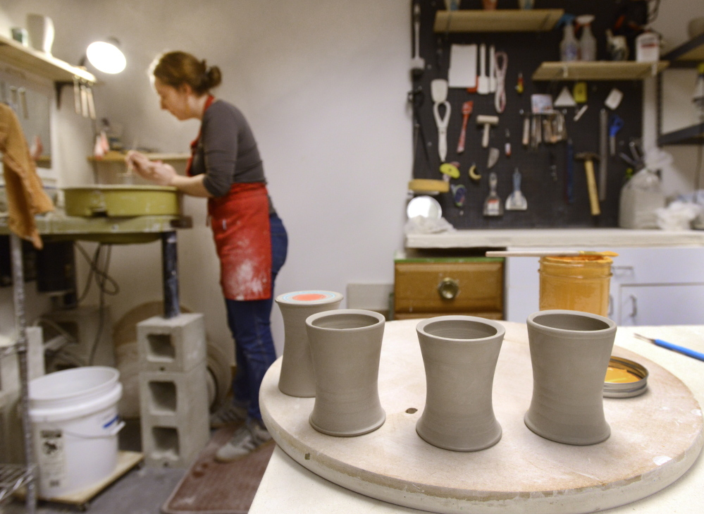 Artist Megan Walsh makes tumblers in studio space at the latest home of the Running With Scissors collective on Anderson Street in Portland. The building has kilns, work tables and wheels for a dozen potters, as well as a print shop, a wood shop, classroom space, a small library and light tables.