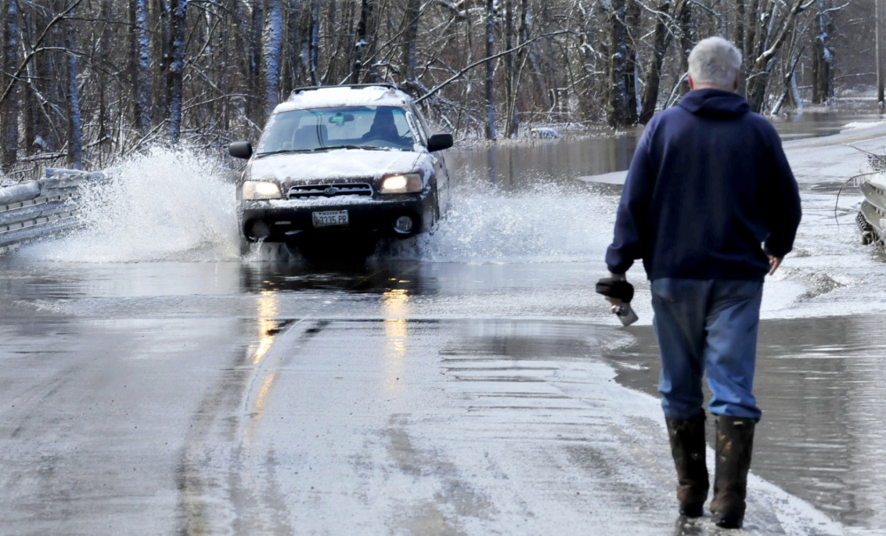 Bob Hueston stops to photograph cars passing through the 6 inches of water that flowed over Prairie Road in Unity on Wednesday. High water from nearby Twenty-five Mile Stream flooded the roadway but cars were able to get through.