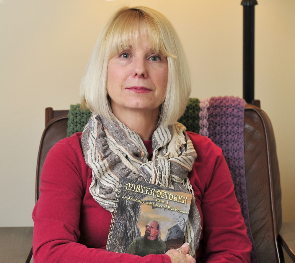 Holly Newstein, holding a book about her late husband, the Westbrook author Rick Hautala, is disappointed that the author's hometown library would not accept his archives.