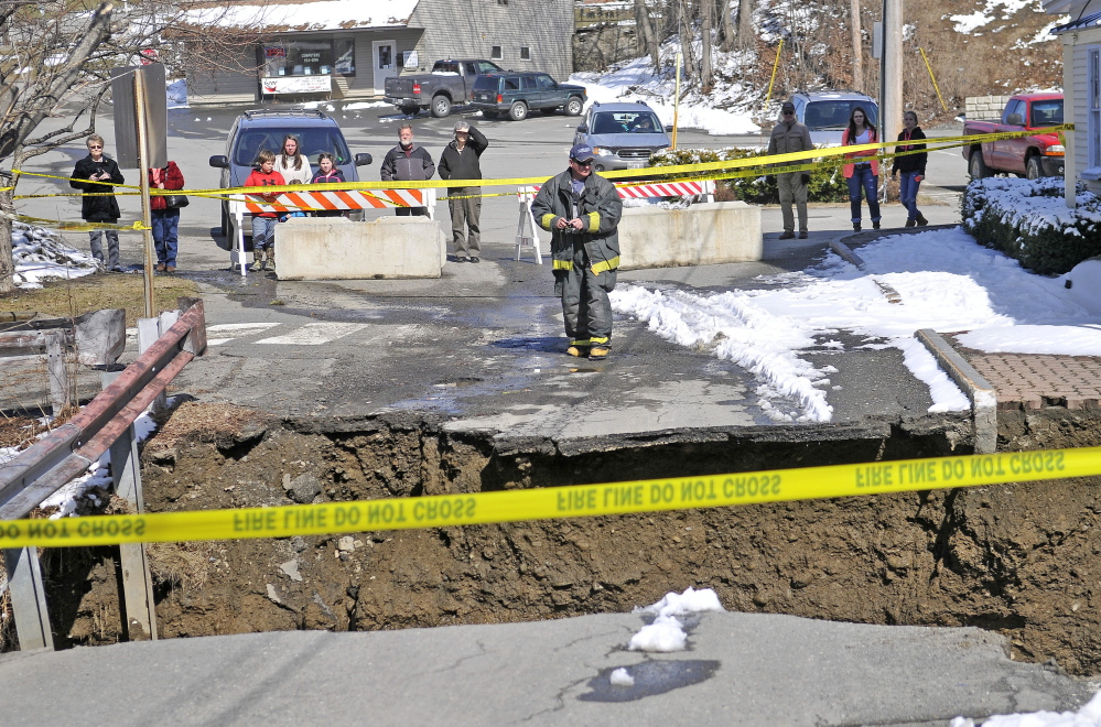 A firefighter stands by the edge of the washed-out connector street between Main Street and Water Street in downtown Dexter on Wednesday. Town Manager Shelley Watson said the town was still assessing flood damages.