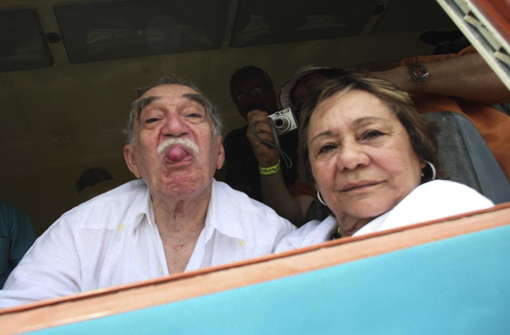 In this May 2007 file photo, Colombia's Literature Nobel Prize winner Gabriel Garcia Marquez sticks out his tongue to photographers as he arrives on a train to Aracataca, his hometown in northeastern Colombia. At right is his wife Mercedes Barcha who accompanied the writer on his first visit to his hometown in 25 years. Marquez died Thursday April 17, 2014 at his home in Mexico City.