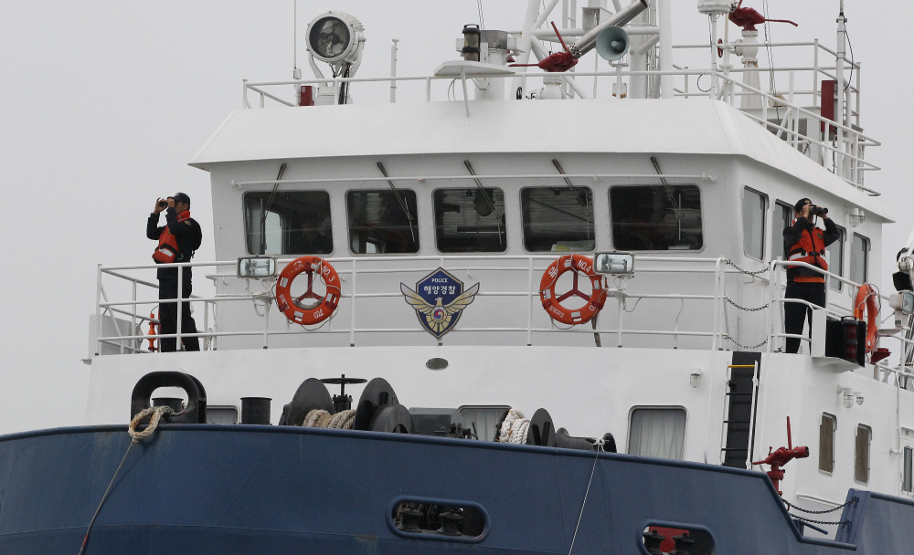 South Korean Coast Guard officers uses binoculars in search for missing passengers aboard their sunken ferry in the water off the southern coast near Jindo, South Korea.