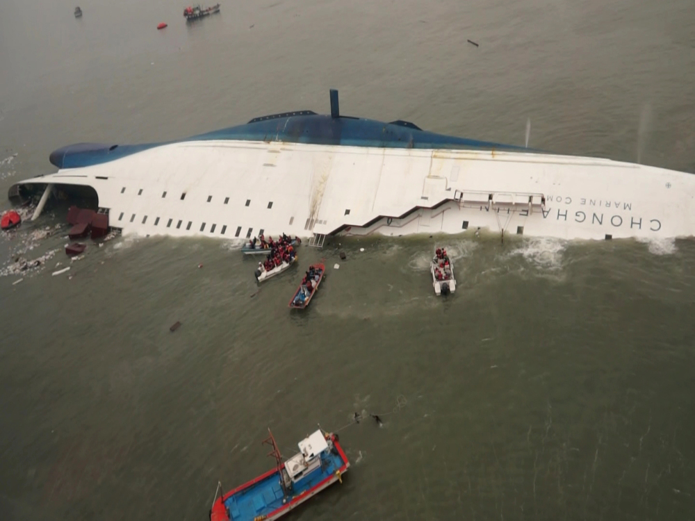 In this photo released by South Korea Coast Guard via Yonhap News Agency, South Korean rescue team boats and fishing boats try to rescue passengers of a ferry sinking off South Korea's southern coast.