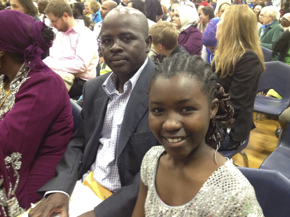 Sara Ali, 11, right, a student at Lyman Moore Middle School and an immigrant from Sudan, gets to see her uncle Abdelrazig Abdelshafie sworn in as a new U.S. citizen.