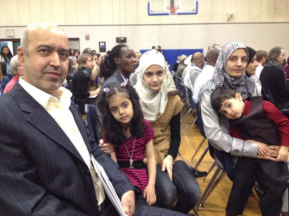 Kosay Alwan, left, came to the United States as a refugee from Iraq five years ago to escape the violence there and applied for his family to become citizens after realizing how safe the United States is. He was naturalized Friday at a ceremony at Lyman Moore Middle School in Portland along with his daughters, 6-year-old Naba and 13-year-old Sahar, and his wife Kawaid. His son, 3-year-old Ali, was born here and is already a citizen.