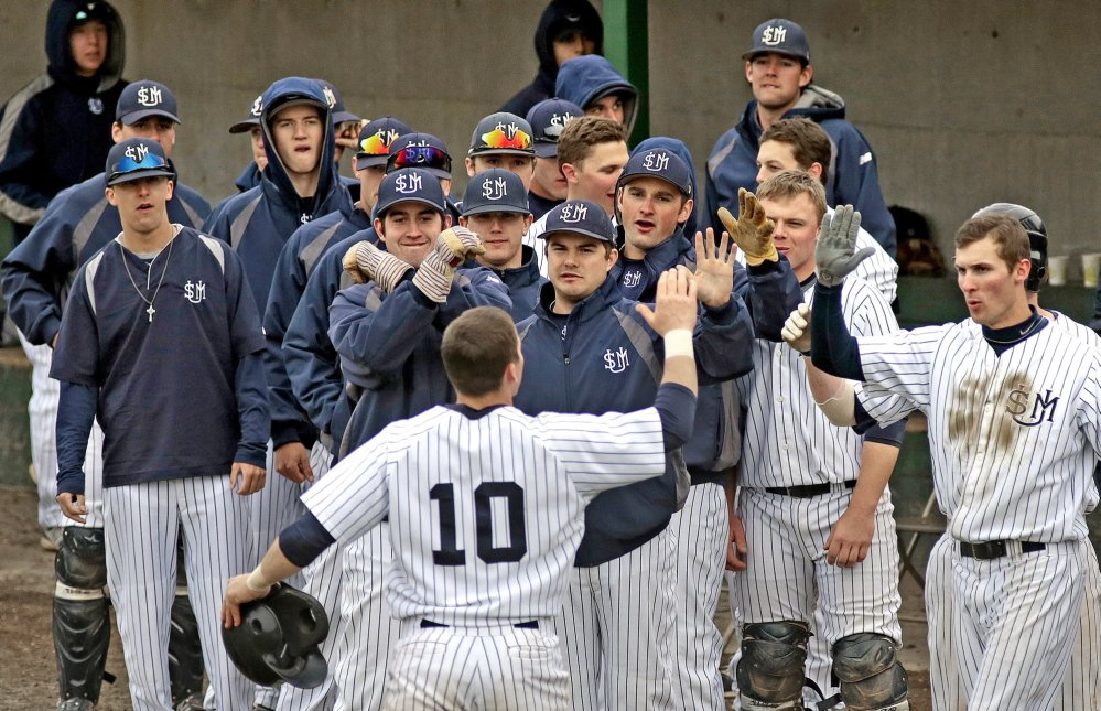 Troy Thibodeau of USM is greeted by his teammates Friday after hitting a solo home run in the fourth inning of the 5-3 victory against Bowdoin at Gorham. The Huskies, who are ranked sixth in the country in Division III, shut down the Polar Bears down the stretch with strong relief pitching.