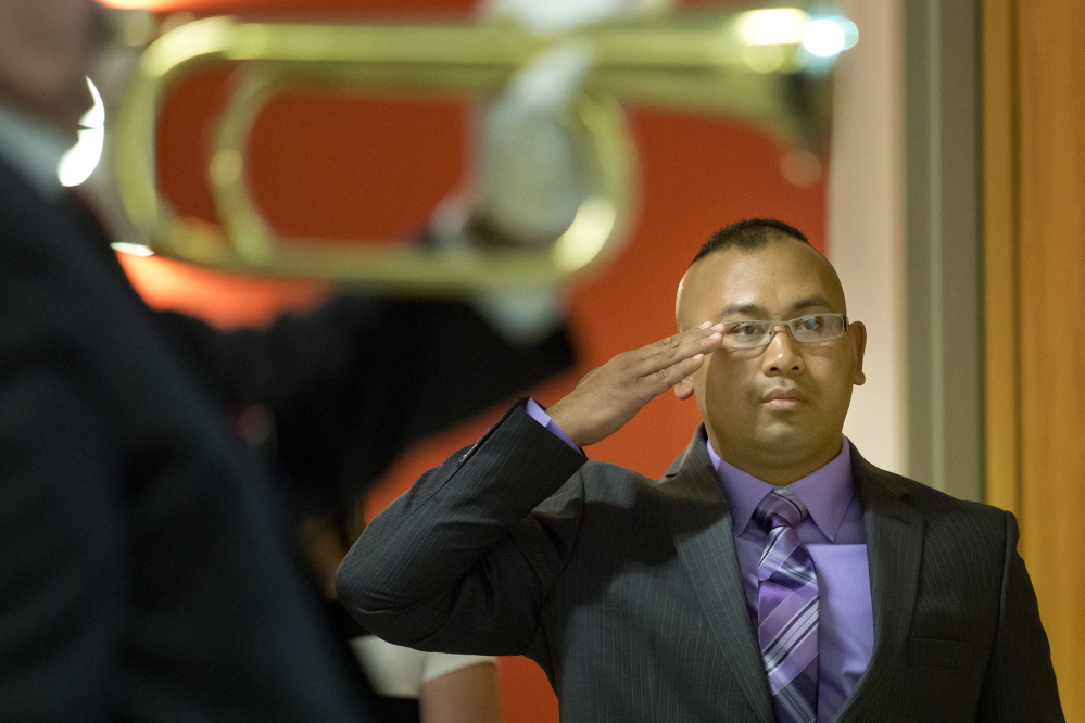 Retired Army Staff Sgt. San Pao stands at attention for the playing of taps during a service to honor Spc. Chris Gelineau, who was killed in combat in Iraq 10 years ago while serving with the Maine Army National Guard's 133rd Engineer Battalion.