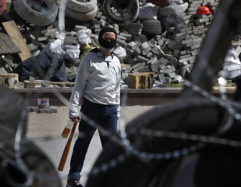 A masked activist walks among barricades Friday at an occupied building in Donetsk, Ukraine. Militants are calling for the interim government in Kiev to resign.