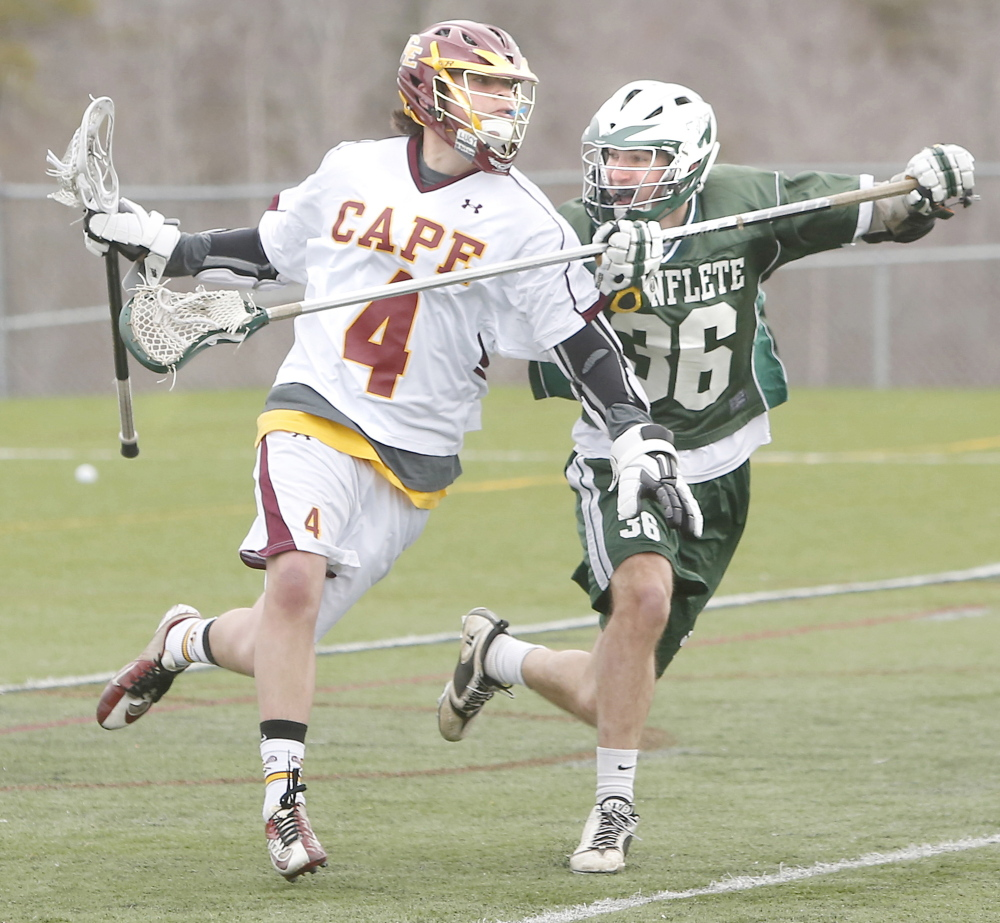 Ben Shea of Cape Elizabeth runs with the ball as Graham Chance of Waynflete attempts to knock it away Friday during Cape Elizabeth's 15-1 victory at home in a Western Maine Conference opener.