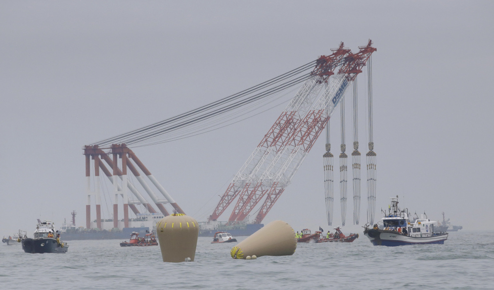 Cranes wait near the buoys installed to mark the sunken 6,852-ton ferry Sewol as fresh questions emerge about whether quicker action by the captain of the doomed ship could have saved lives.