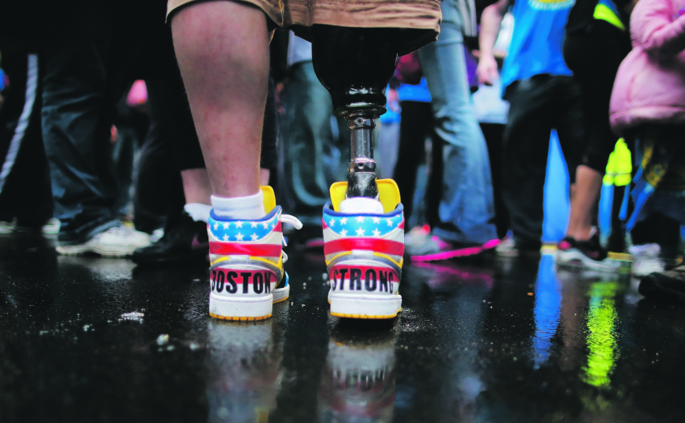 "The shoes of 2013 Boston Marathon bombing survivor J.P. Norden read ""Boston Strong"" as he stands at the finish line on Tuesday, the one-year anniversary of the bombings. J.P. and his brother Paul, also a bombing survivor, took part in the final portion of the ""Legs for Life Relay,"" joining family members and friends who walked the entire marathon route to raise money for children needing prosthetic limbs."