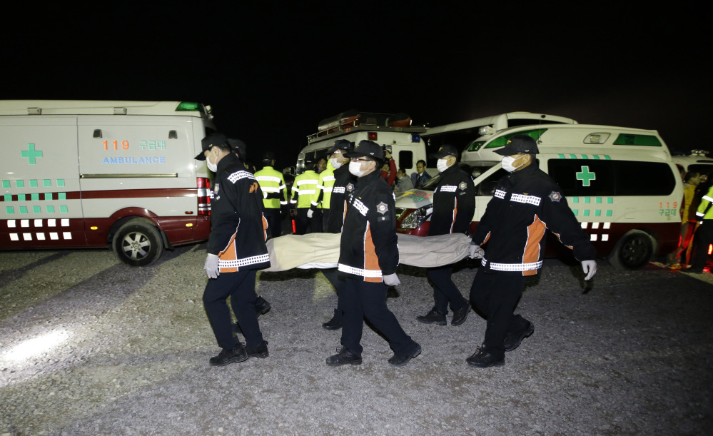 The body of a passenger aboard the Sewol ferry which sank in the water off the southern coast, is carried by rescue workers upon its arrival at a port in Jindo, south of Seoul, South Korea, Saturday.