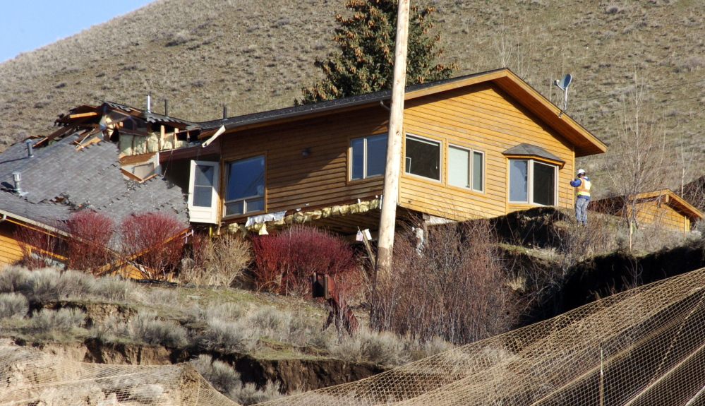 A worker inspects damage to a house at the top of a slow-motion landslide in Jackson, Wyo., on Saturday.