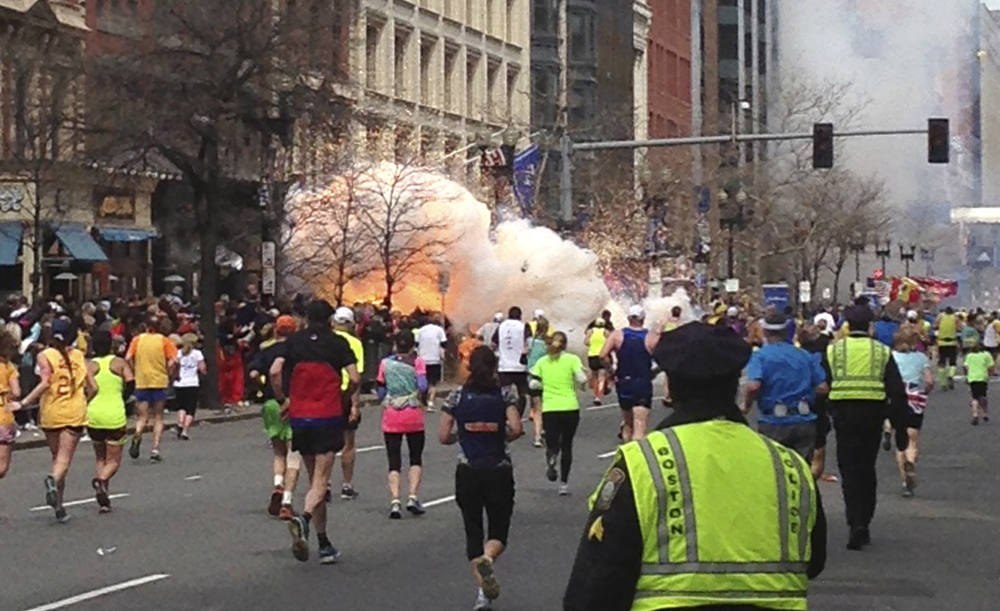 An explosion erupts near the finish line of the Boston Marathon on April 15, 2013. It was followed by another 12 seconds later. Among those who rushed to victims' aid was John Mixon of Ogunquit, who helped rip openings in a crowd-control barrier that was obstructing first responders. Mixon has endured his father's death and a near-fatal heart attack himself in the year since, but he'll be back at the marathon finish line Monday supporting Run for the Fallen participants.