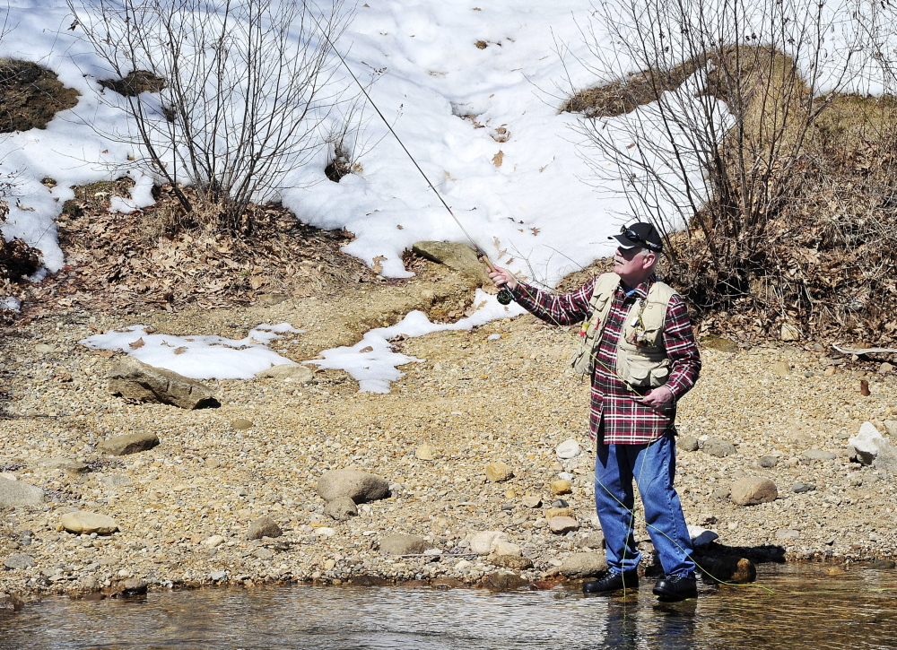 With snow still on the ground behind him, Falmouth's Bruce Wilson does what he's done for the past 30 years – fishing on opening day, this time at Songo Locks in Naples.