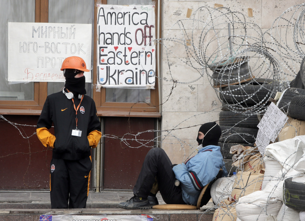 Masked pro-Russian insurgents guard a barricade Saturday at a building they had seized in Donetsk, Ukraine. Militants want the acting pro-Western government to resign.