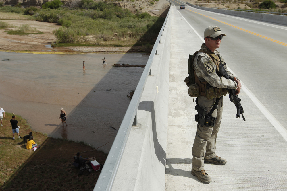 Justin Giles of Wasilla, Alaska, stands guard on a bridge over the Virgin River during a rally in support of Cliven Bundy near Bunkerville, Nev., on Friday.