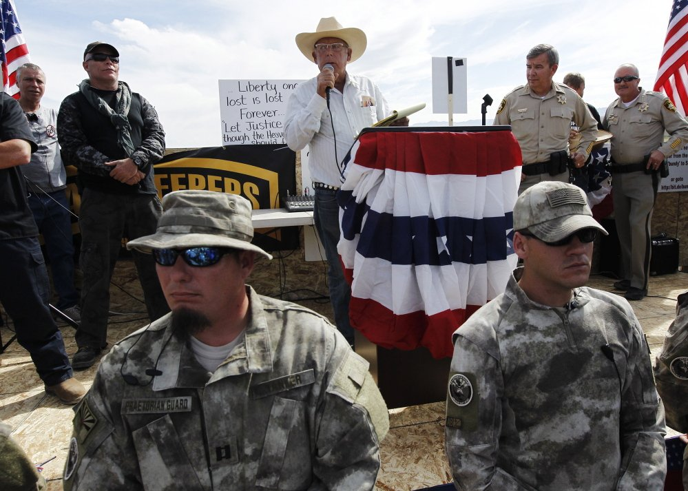 Rancher Cliven Bundy, center, addresses his supporters alongside Clark County Sheriff Doug Gillespie, right, on April 12, saying the BLM had agreed to cease the roundup of his family's cattle.