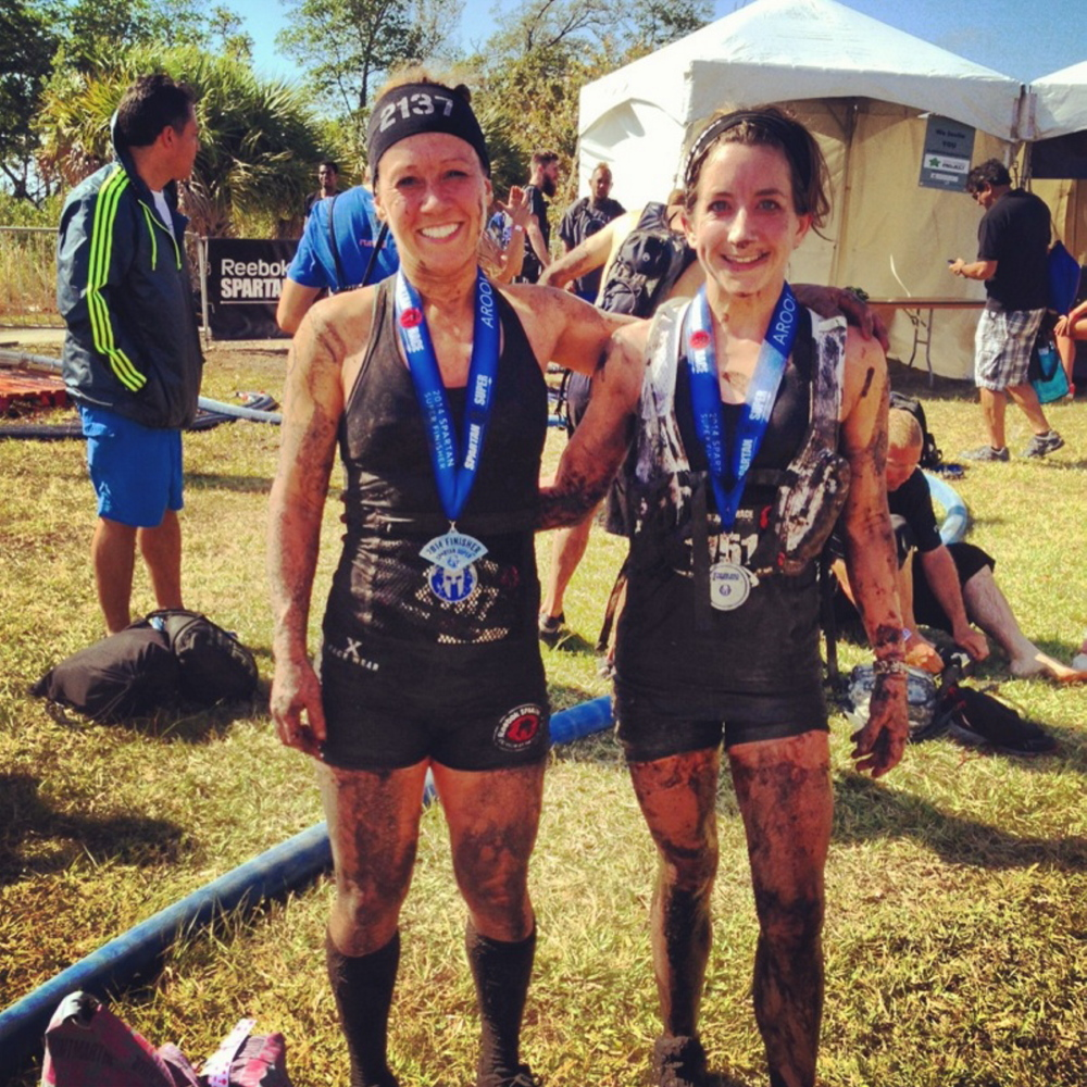 Debbie Moreau, left, and Natasha Leighton celebrate their finishes in the women's elite division of the Miami Spartan Super race.