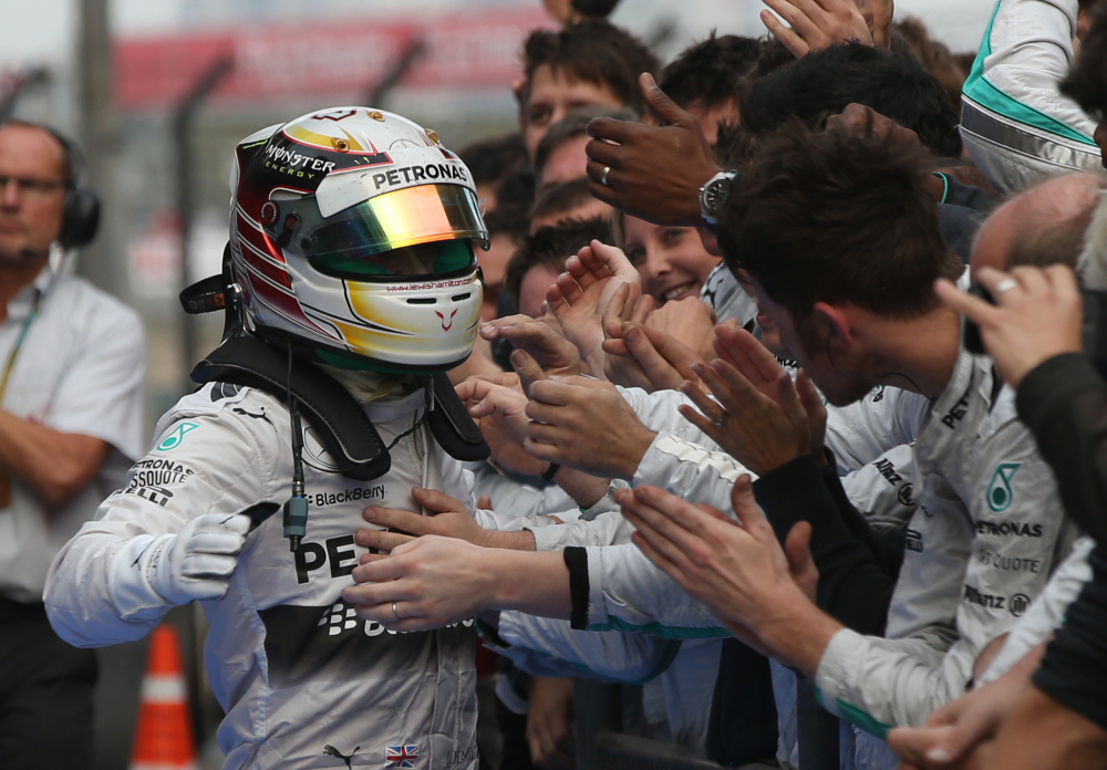 Mercedes driver Lewis Hamilton of Britain, left, is congratulated by his team members after the Chinese Formula One Grand Prix at Shanghai International Circuit in Shanghai on Sunday.