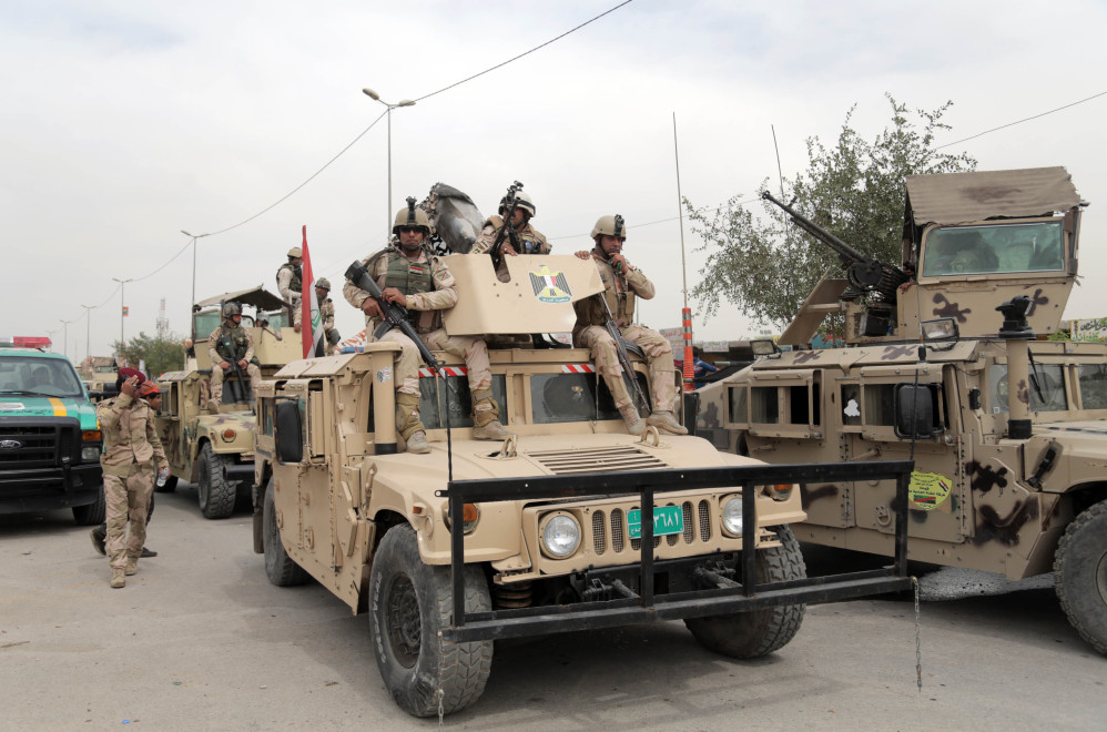 Iraqi security forces guard the main gate of a Shiite private college following a deadly suicide attack, in Baghdad's eastern neighborhood of Ur, Iraq, on Sunday.