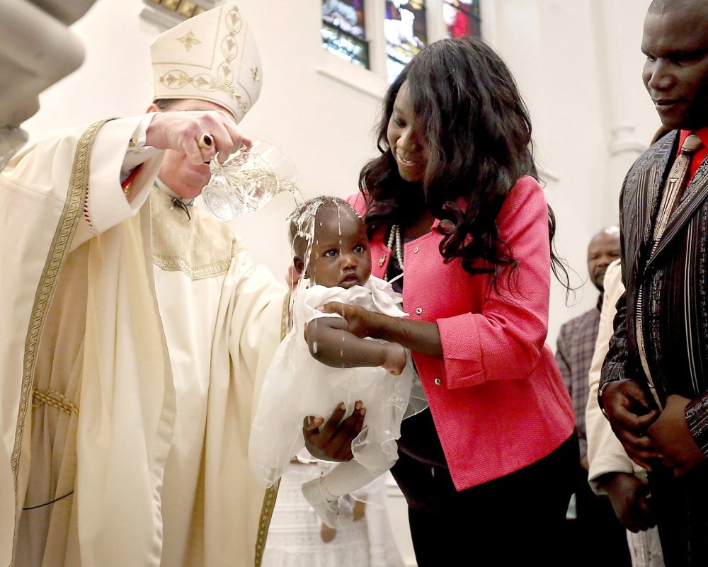 The Most Rev. Robert P. Deeley baptizes Angelina Sebit during Easter Mass at the Cathedral of the Immaculate Conception in Portland on Sunday. Her godmother, Rita Achiro, holds her, while the baby's father stands at right.