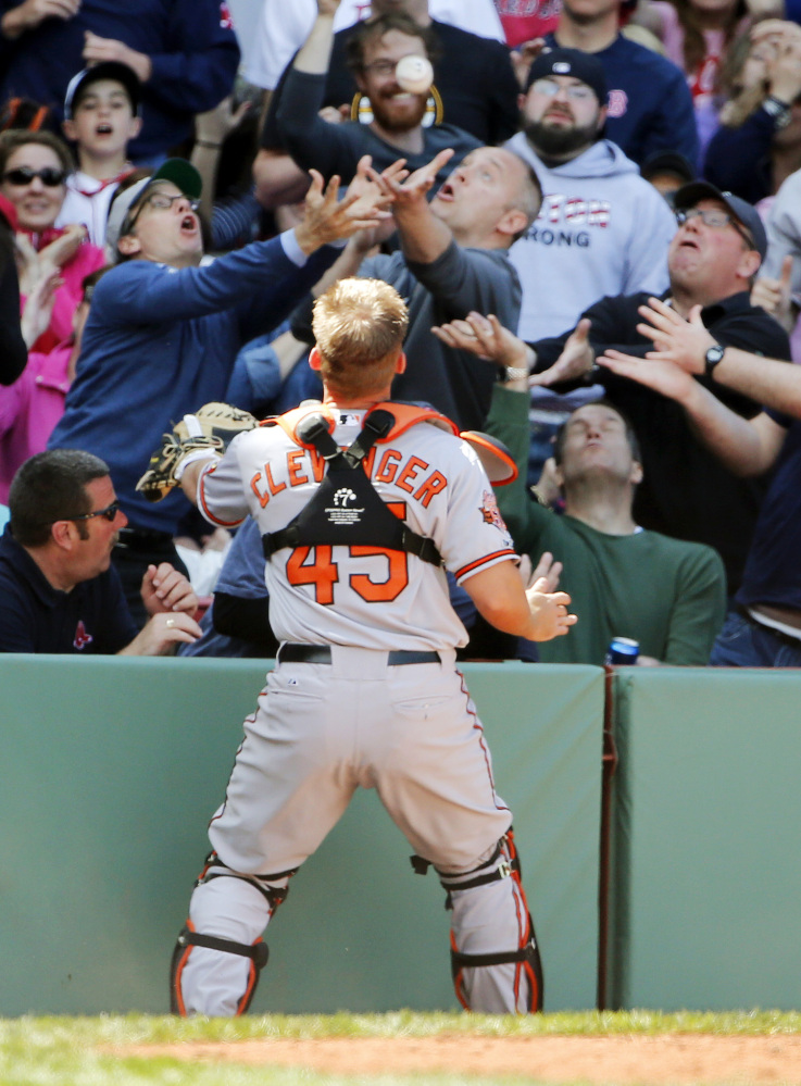 Baltimore Orioles catcher Steve Clevenger stands by as fans go for a foul popup by Red Sox Jackie Bradley Jr. during the ninth inning in Baltimore's 7-6 win at Fenway on Monday.