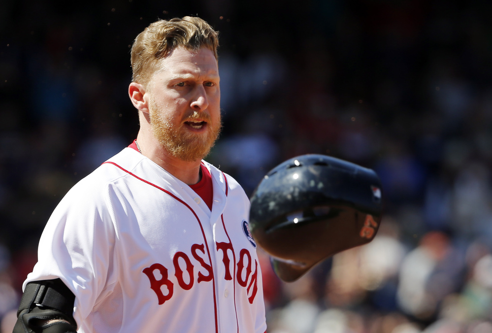 Boston's Mike Carp tosses his helmet in frustration after his ninth-inning groundout with two runners on sealed a 7-6 loss to Baltimore at Fenway Park on Monday