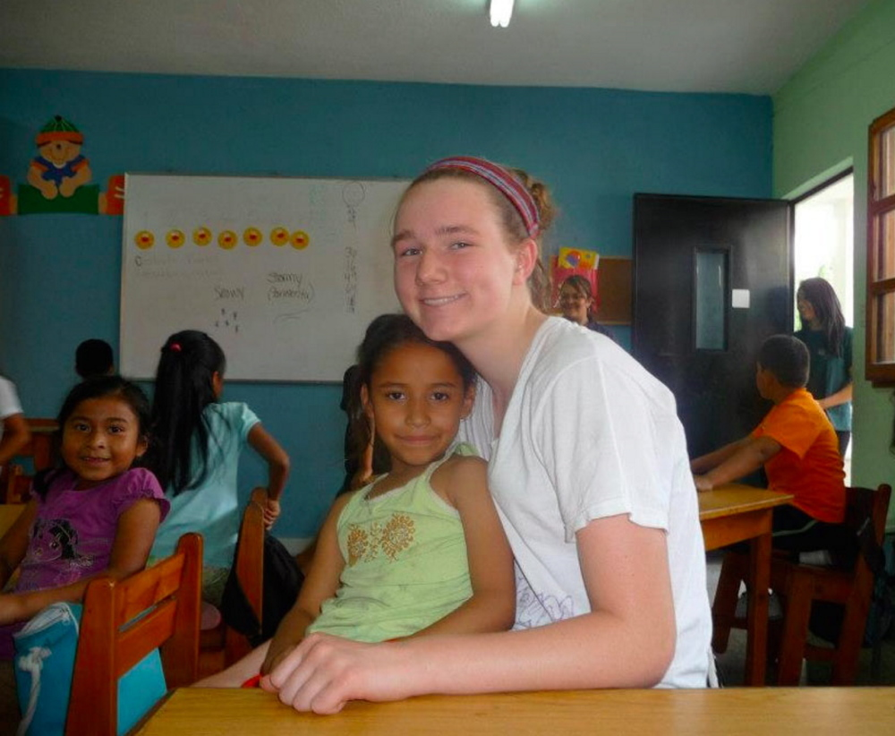 Caroline Maker poses with a student at Safe Passage in Guatemala while visiting her older sister, who was volunteering there in April 2013. Caroline, 15, organized a group of fellow sophomores from Greely High School to spend their spring break volunteering at the program.