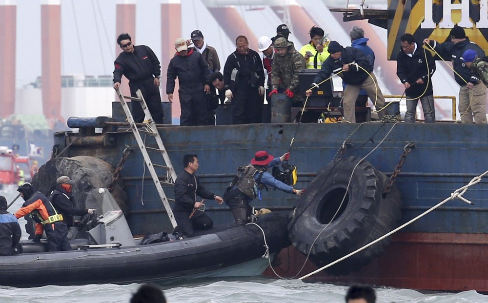 U.S. technicians hand off a remotely-operated vehicle to South Korean rescue team members to be used for searching for passengers of the sunken ferry Sewol in the water off the southern coast near Jindo, South Korea, on Monday.